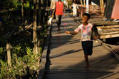 The Indonesian boy runs on a wooden roadway. Stock Photos