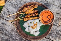 Indonesian chicken satay or Sate Ayam served with lontong, soy sauce and peanut sauce lifestyle food. Indonesian chicken satay or Sate Ayam served with lontong stock photos