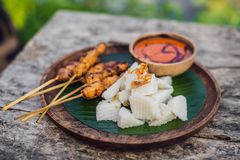 Indonesian chicken satay or Sate Ayam served with lontong, soy sauce and peanut sauce lifestyle food. Indonesian chicken satay or Sate Ayam served with lontong stock images