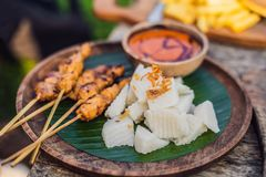 Indonesian chicken satay or Sate Ayam served with lontong, soy sauce and peanut sauce lifestyle food royalty free stock photography