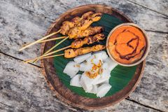 Indonesian chicken satay or Sate Ayam served with lontong, soy sauce and peanut sauce lifestyle food. Indonesian chicken satay or Sate Ayam served with lontong stock photo