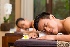 Indonesian couple having wellness massage. Indonesian Asian couple men and women in wellness beauty spa having aroma therapy massage with essential oil, looking Royalty Free Stock Photos