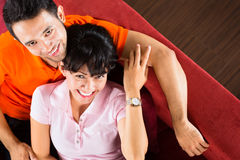 Asian couple at home on sofa Royalty Free Stock Photography