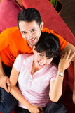 Asian couple at home on sofa Stock Photos