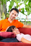 Asian couple in spacious home on sofa Stock Photo