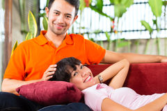 Asian couple in spacious home on sofa Stock Image