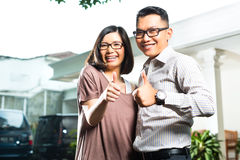 Asian homeowner couple in front of home Stock Images