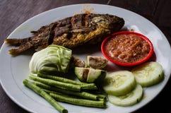 Indonesian dish ikan goreng fried fish close-up.  royalty free stock photography