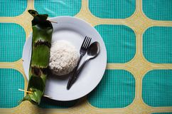 Indonesian dish PEPES IKAN closed in banana leaf - top view with rice and copy space right.  Royalty Free Stock Images