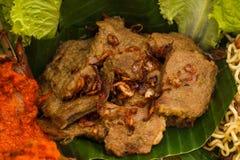 Indonesian dish rendang on nasi tumpeng. Close up portrait of indonesian dish rendang on nasi tumpeng royalty free stock images