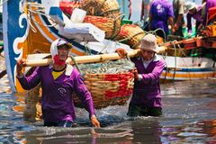 Indonesian dockers unload traditional fishing boat. Jembrana, Bali Island, Indonesia - September 20, 2015: A way of life, earning money in Bali. In Perancak Royalty Free Stock Image
