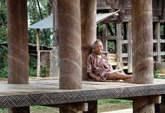 Indonesian elderly man sits under the floor of tongkonan traditional house in Tana Toraja Stock Image