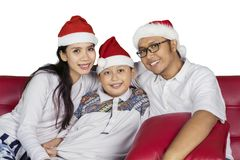 Indonesian family wearing Santa hat on studio. Indonesian family wearing Santa Claus hat while looking at the camera, isolated on white background Royalty Free Stock Photography
