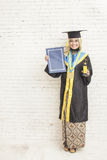 Indonesian female graduate student  wearing graduation gown whil Royalty Free Stock Photo