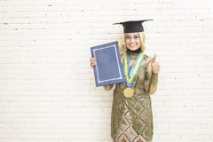 Indonesian female graduated student in traditional clothes smili Royalty Free Stock Photo