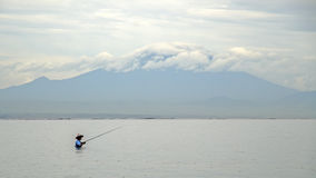 Indonesian fisherman catches a fish during a tropical rain. Stock Image
