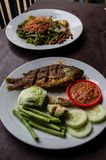 Indonesian food: Ikan goreng fried fish and kankung plecing spicy water spinach dish.  Stock Photo
