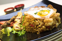 Indonesian Fried Rice. Exotic dish of Indonesian fried rice made with chicken and shrimp, topped with a fried egg. Chicken and beef satays are served on the side Royalty Free Stock Images