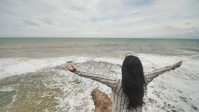 Indonesian girl enjoys life with outstretched hands on the rocky shore on the island of Bali. Indonesian girl enjoys life with outstretched hands on the rocky stock video