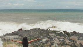 Indonesian girl enjoys life with outstretched hands on the rocky shore on the island of Bali. Indonesian girl enjoys life with outstretched hands on the rocky stock footage