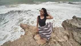 Indonesian girl enjoys life with outstretched hands on the rocky shore on the island of Bali. Indonesian girl enjoys life with outstretched hands on the rocky stock video footage