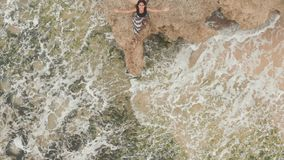 Indonesian girl enjoys life with outstretched hands on the rocky shore on the island of Bali. Shooting with the height.  stock video