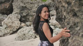 Indonesian girl posing on a beautiful and rocky beach in Bali. Idonezia. Indonesian girl posing on a beautiful and rocky beach in Bali. Idonezia stock footage