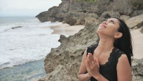 Indonesian girl praying on a rocky Bali beach. Indonesian girl praying on a rocky Bali beach stock footage