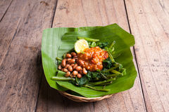 Indonesian green salad with fried peanuts. Spicy and lime in a basket Royalty Free Stock Photography