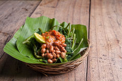 Indonesian green salad on wood table. Indonesian green salad with fryied penuts spicy and lime in a basket Stock Photos
