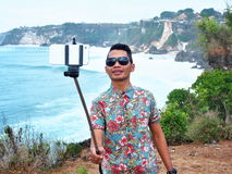 Indonesian Guy With Selfie Stick. Satisfied Indonesian young man wearing sun glasses near by the sea during g the beautiful sunny day with the swlfie stick and Royalty Free Stock Photos