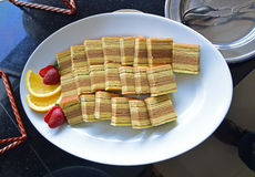 Indonesian kueh lapis served on a white plate with cut fruits on side Stock Photography