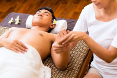 Indonesian man having wellness hand massage Stock Photo