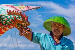 An indonesian man holding a big kite with a dragon head. An indonesian man in green sunhat holding a big red kite with a dragon head, Sanur, Bali, Indonesia Royalty Free Stock Images