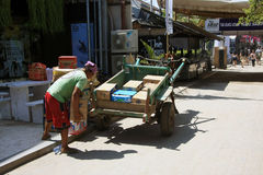 Indonesian man loading boxes on to horse and cart in Gili Trawangan Royalty Free Stock Image