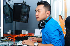 Indonesian man in recording studio. Asian musician, producer or mixer in sound studio royalty free stock photography