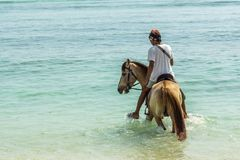 Indonesian man riding a horse in the shallow water close to the. Indonesian man riding a horse in the blue and green shallow water close to the beach, april 24 stock photo