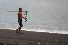 Indonesian man with a speargun. Indonesian man with spearfishing equipment walking on a black sand beach near Batuputih village on north Sulawesi stock photography