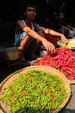 Indonesian market. BOGOR, INDONESIA - JULY 4: Man selling chilli peppers on a market on July 4, 2011 in Bogor, Indonesia Royalty Free Stock Images