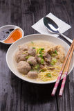 Indonesian Meatball Bakso Noodle with sweet soy sauce and chilli sauce sprinkle with green onion. On wood base Stock Photo