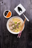Indonesian Meatball Bakso Noodle with sweet soy sauce and chilli sauce sprinkle with green onion. On wood base Royalty Free Stock Photography