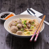 Indonesian Meatball Bakso Noodle with sweet soy sauce and chilli sauce sprinkle with green onion. On wood base Royalty Free Stock Images