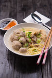 Indonesian Meatball Bakso Noodle with sweet soy sauce and chilli sauce sprinkle with green onion. On wood base Royalty Free Stock Photos