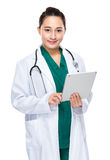 Indonesian mixed race woman doctor use digital tablet Stock Image