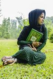 Indonesian moslim girl with a quran. Indonesian moslim girl in a black scarf holding quran Stock Images