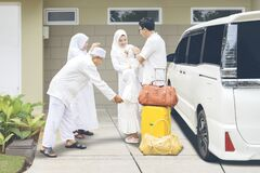 Indonesian muslim family with travel bags and a suitcase waving goodbye to parents