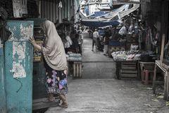 Indonesian Muslim woman wearing the veil walks a back alley in Jakarta, Indonesia stock photography