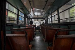 Indonesian passengers commute in an old empty bus in Jakarta, Indonesia stock photography