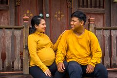 Indonesian pregnant wife sits with her husband outside their traditional house stock image