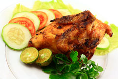 Indonesian roasted chicken. Roasted chicken with vegetables on white background Stock Image